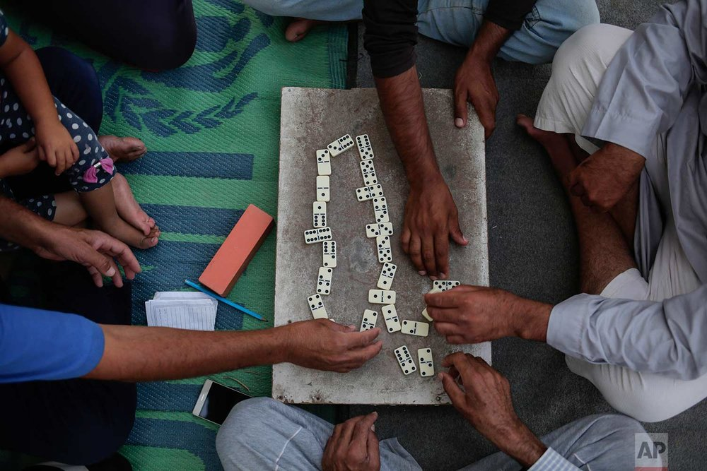 In this Saturday, July 22, 2017 photo, displaced Sunni Arabs play a game in the Hassan Sham camp in northern Iraq. (AP Photo/Bram Janssen)