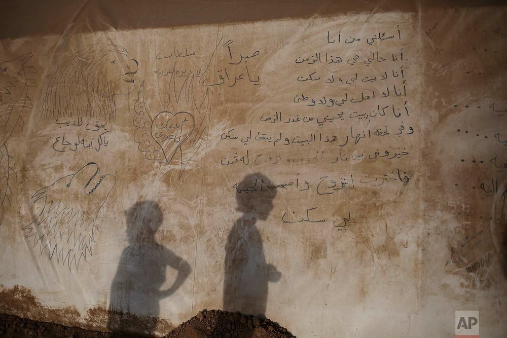 """In this Sunday, July 25, 2017 photo, the shadows of two boys are seen on the side of a tent inside the Khazer camp for displaced people in Northern Iraq. A poem is written in the side of the tent: """"Ask me who I am, I am talking for myself. I am the one who doesn't have a house or a home. I'm the one without relatives and a country. I used to have a house protecting me from the treason of time. In a moment this house collapsed and there's something left for me. I had to choose between the flames of war and the consequences of displacement. I chose displacement and the tent became my home."""" (AP Photo/Bram Janssen)"""