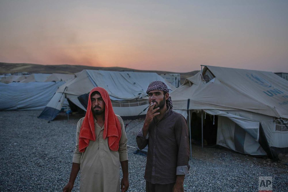 In this Friday, July 21, 2017 photo, Younes Abdullah, left, and his nephew Rakan Hamid Jasim stand inside the Chamakor camp for displaced people in Northern Iraq. They both want to return to their homes in the town of Zummar, currently under Kurdish control, but Kurdish security forces don't allow them to return. The two relatives lived under Islamic State rule for almost three years. (AP Photo/Bram Janssen)