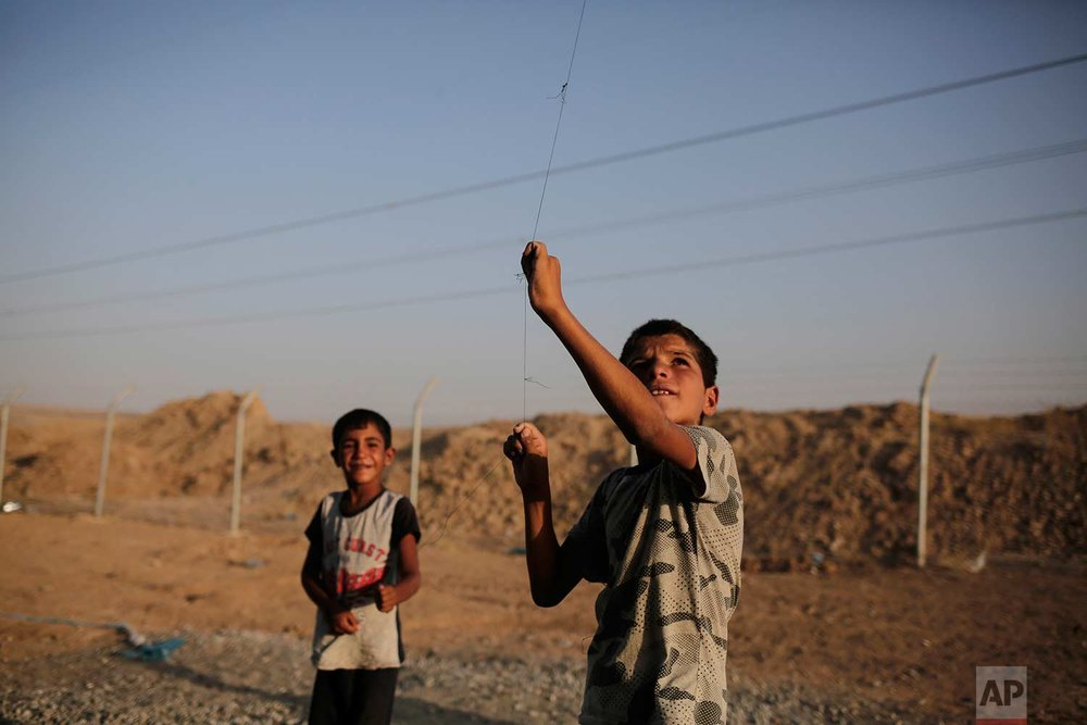 In this Friday, July 21, 2017 photo, seven year-old Omar from Mosul flies a kite in the Chamakor camp for displaced people in northern Iraq. Many displaced can't return to their homes in Iraq's second largest city as their houses are destroyed by air strikes. (AP Photo/Bram Janssen)