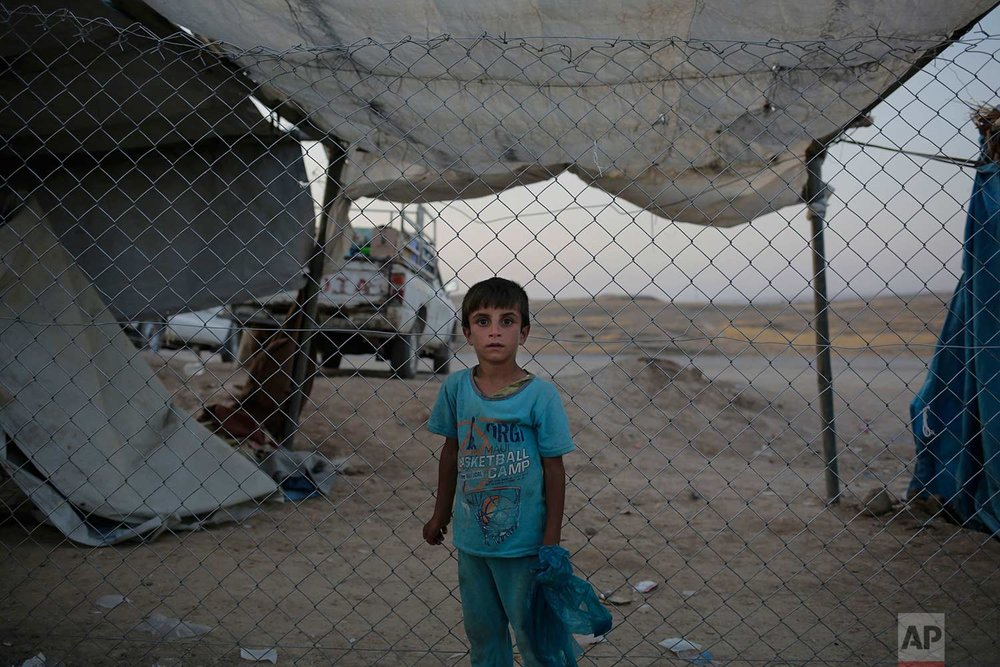 In this Friday, July 21, 2017 photo, a boy stands in front of a fence of the Chamakor camp in northern Iraq. Kurdish security forces who control the camp aren't allowing Sunni Arabs to return to their homes, which are now under Kurdish control. (AP Photo/Bram Janssen)