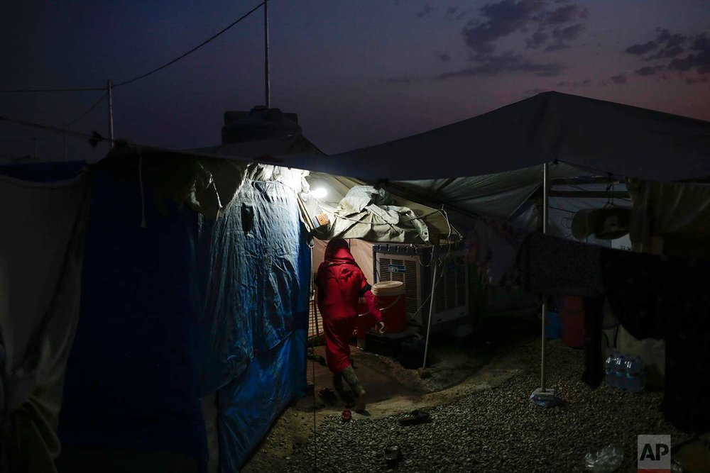 In this Wednesday, Aug. 2, 2017 photo, a girl enters her tent at night in the Hassan Sham camp for displaced people in northern Iraq. (AP Photo/Bram Janssen)