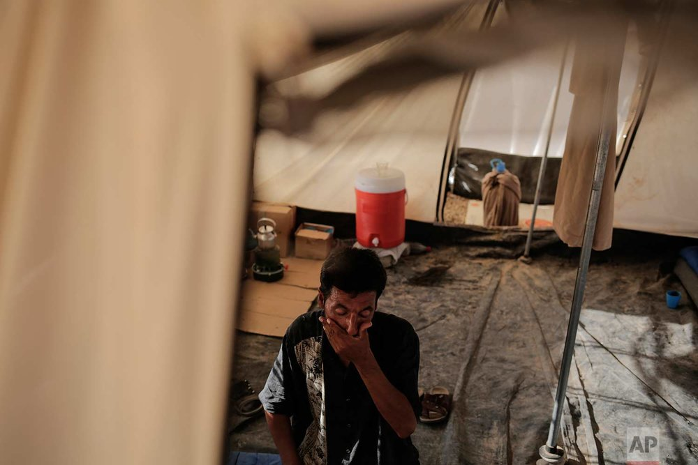 In this Tuesday, Aug. 1, 2017 photo, Abu Abdullah Fathi from west Mosul sits inside his tent in the Chamokor camp in northern Iraq. Abu Abdullah and his wife and five children can't return to their home in the Tanak neighborhood after it was destroyed by an air strike. (AP Photo/Bram Janssen)