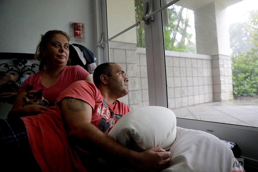 Javier Garcia, right, and his wife Marissa Soto sit with their neighbor's dog Ilito as they ride out Hurricane Irma in a shelter in Naples, Fla., Sunday, Sept. 10, 2017. (AP Photo/David Goldman)