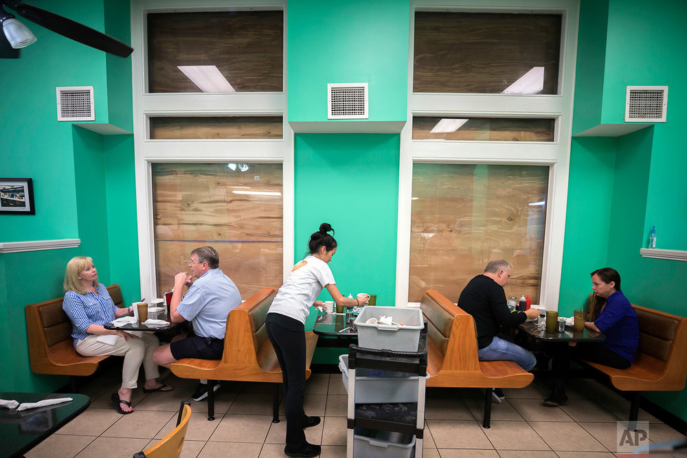Henry's Restaurant manager Nhi Brayman, center, cleans a table while customers eat breakfast behind boarded up windows, Sunday, Sept., 10, 2017, in downtown Savannah, Ga. (AP Photo/Stephen B. Morton)