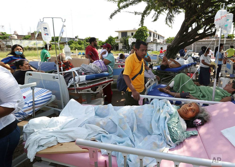 Evacuated patients lie on their hospital beds shaded by a tree, in the aftermath of a massive earthquake in Juchitan, Oaxaca state, Mexico, Friday, Sept. 8, 2017. One of the most powerful earthquakes ever to strike Mexico hit off its southern Pacific coast, causing dozens of fatalities, toppling houses, government offices and businesses. (AP Photo/Luis Alberto Cruz)