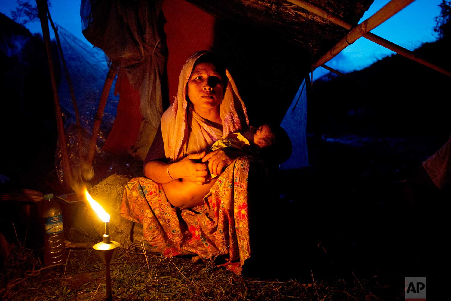 A Rohingya ethnic minority woman cradles her child at a temporary makeshift camp after crossing over from Myanmar into the Bangladesh side of the border, near Cox's Bazar's Gundum area, Saturday, Sept. 2, 2017. U.N. spokesman Stephane Dujarric told reporters at U.N. headquarters on Friday that while many of the 270,000 Rohingyas who have fled violence in Rakhine state in the past two weeks initially arrived in Bangladesh by land, more are now making the journey by boat. (AP Photo/Bernat Armangue)