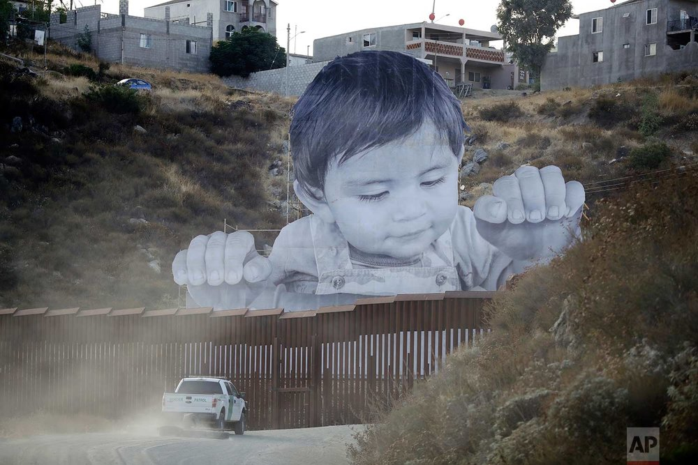 A U.S. Border Patrol vehicle drives in front of a mural in Tecate, Mexico, just beyond a border barrier in Tecate, Calif., on Friday, Sept. 8, 2017. A French artist aiming to prompt discussions about immigration erected the 65-foot-tall image of a Mexican boy, pasting it to scaffolding built in Mexico. The installation overlooks a section of wall on the California border. (AP Photo/Gregory Bull)