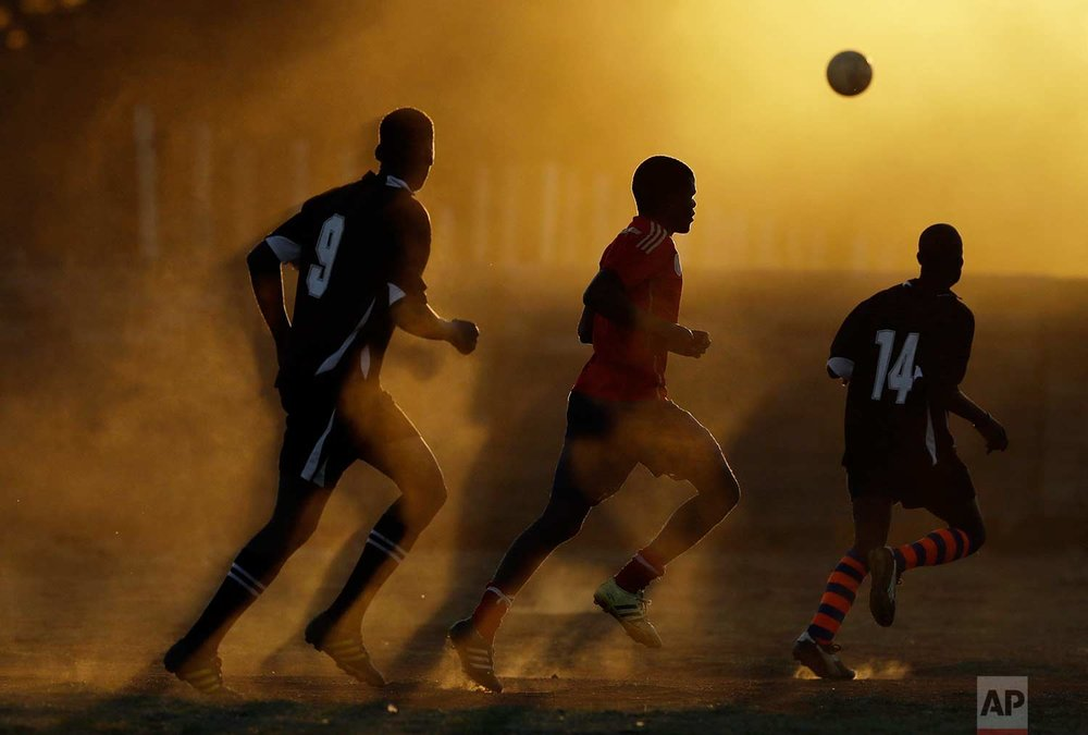 Players chase the ball on a dusty field during their soccer match in Nigel, east of Johannesburg, South Africa, Sunday, Sept. 3, 2017. (AP Photo/Themba Hadebe)