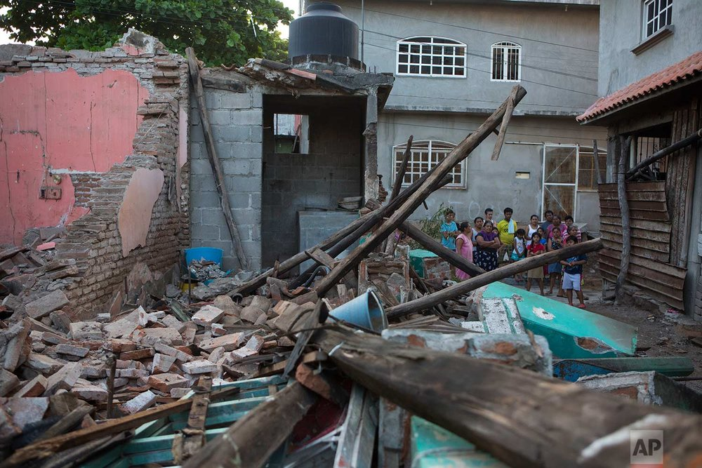 Neighbors look at a home destroyed by a massive earthquake, in Juchitan, Oaxaca state, Mexico, Saturday, Sept. 9, 2017. The 8.1 quake off the southern Pacific coast just before midnight Thursday toppled hundreds of buildings in several states. Hardest-hit was Juchitan, where a third of the city's homes collapsed or were uninhabitable. (AP Photo/Rebecca Blackwell)