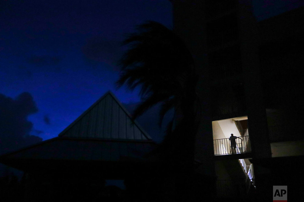 Laura Raymond walks down the stairs with a flashlight while leaving her mother-in-law's fourth floor apartment where she rode out Hurricane Irma with her family to return to their low lying home a mile away in Marco Island, Fla., Monday, Sept. 11, 2017. (AP Photo/David Goldman)