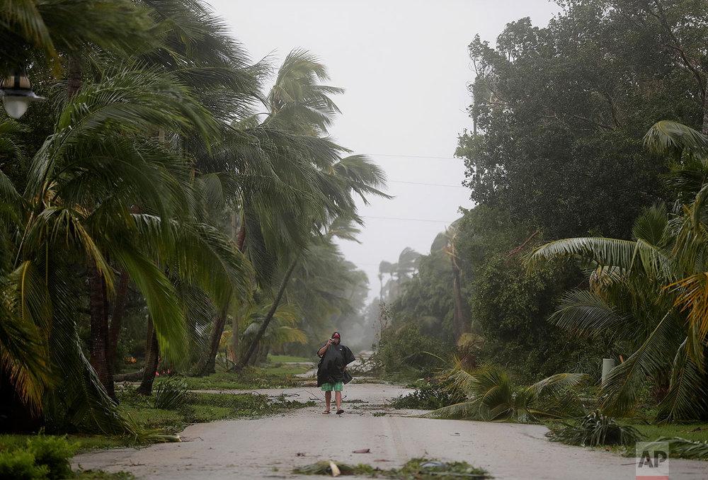 A person walks through a street lined with debris and fallen trees as Hurricane Irma passes through Naples, Fla., Sunday, Sept. 10, 2017. (AP Photo/David Goldman)
