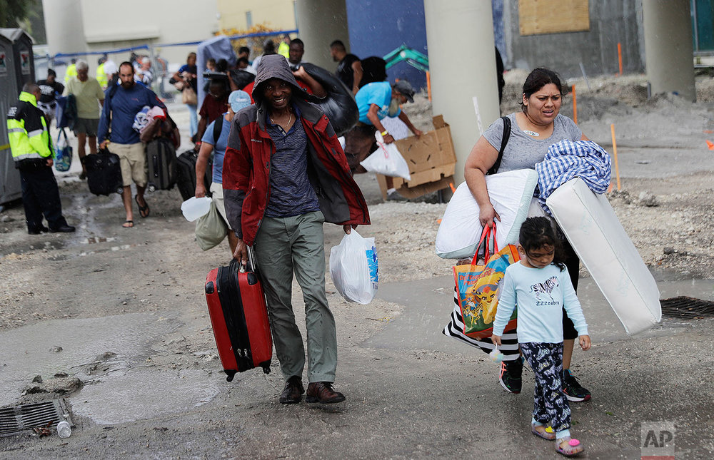 Evacuees are moved to another building with more bathrooms while sheltering at Florida International University ahead of Hurricane Irma in Miami, Saturday, Sept. 9, 2017. (AP Photo/David Goldman)