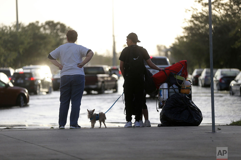 Evacuees leave the Germain Arena, which was used as an evacuation shelter for Hurricane Irma, which passed through yesterday, in Estero, Fla., Monday, Sept. 11, 2017. (AP Photo/Gerald Herbert)