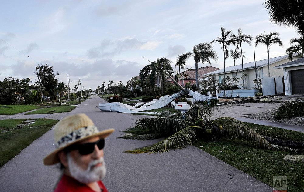 A fallen palm tree and a roof litters a street as Rick Freedman checks his neighborhood's damage from Hurricane Irma in Marco Island, Fla., Monday, Sept. 11, 2017. (AP Photo/David Goldman)