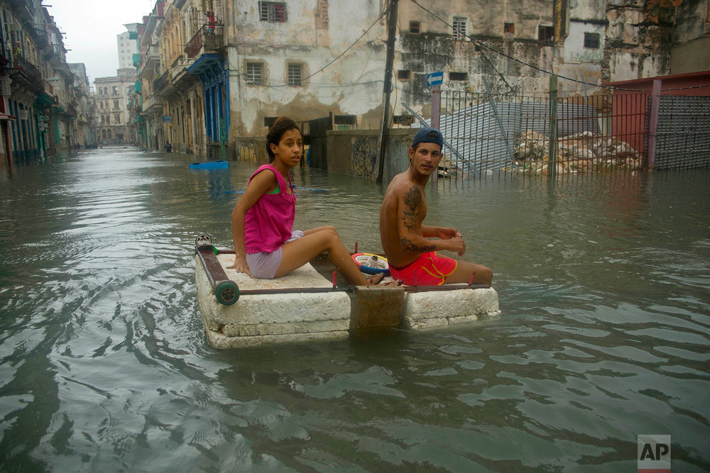 A couple floats down a flooded street in Havana atop a large piece of styrofoam, after the passing of Hurricane Irma in Cuba, Sunday, Sept. 10, 2017. The powerful storm ripped roofs off houses, collapsed buildings and flooded hundreds of miles of coastline after cutting a trail of destruction across the Caribbean.There were no immediate reports of deaths in Cuba, a country that prides itself on its disaster preparedness, but authorities were trying to restore power and clear roads. (AP Photo/Ramon Espinosa)