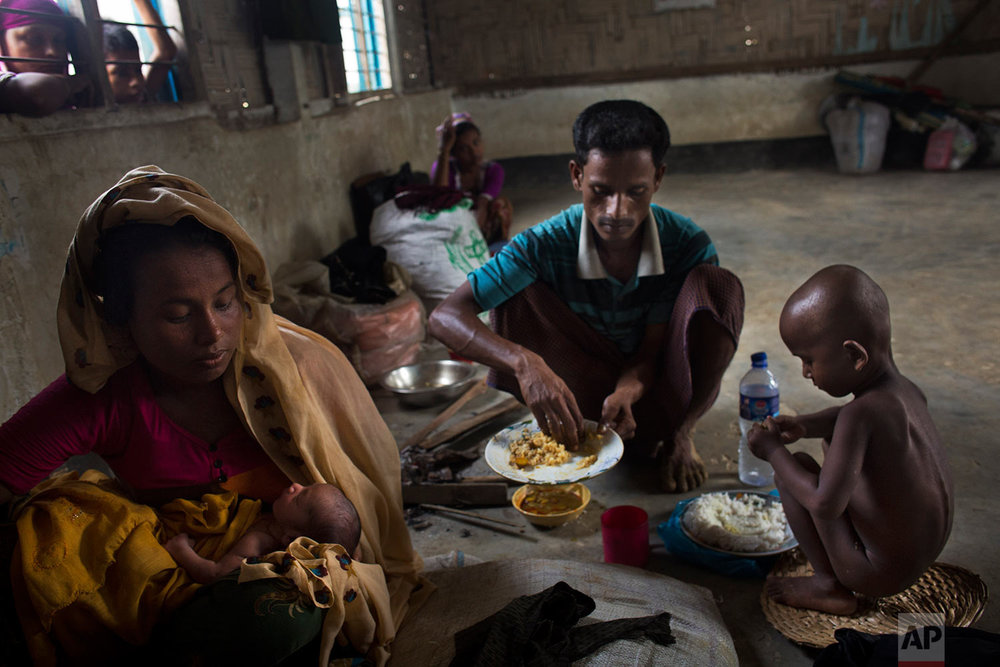In this Thursday, Sept. 7, 2017 photo, 25-year-old Rohingya Muslim woman Zahida Begum cradles her few-hours-old son who she gave birth to alone in the toilet outside the room, as her husband Abdur Rahman mixes a plate of rice for his wife at Kutupalong refugee camp, Bangladesh. Rahman had to leave his ailing wife and go search for food. He came back with the plate of rice and small bowl of curry. That food is the first food his wife and son shared all day. (AP Photo/Bernat Armangue)