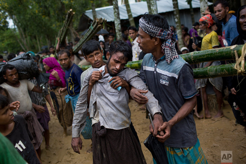 Kifawet Ullah is helped by other newly arrived Rohingya after he collapsed while waiting to have his token validated in order to collect a bag of rice distributed by aid agencies in Kutupalong, Bangladesh, Saturday, Sept. 9, 2017. (AP Photo/Bernat Armangue)