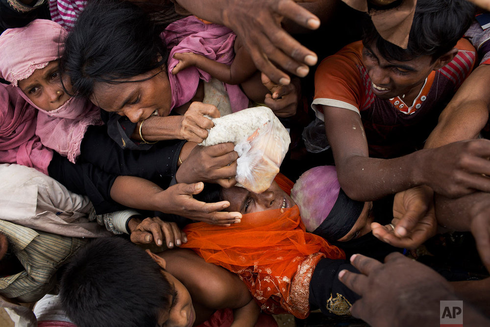 Rohingya Muslims, newly arrived from Myanmar, scuffle for puffed rice food rations donated by local volunteers in Kutupalong, Bangladesh, Saturday, Sept. 9, 2017. (AP Photo/Bernat Armangue)