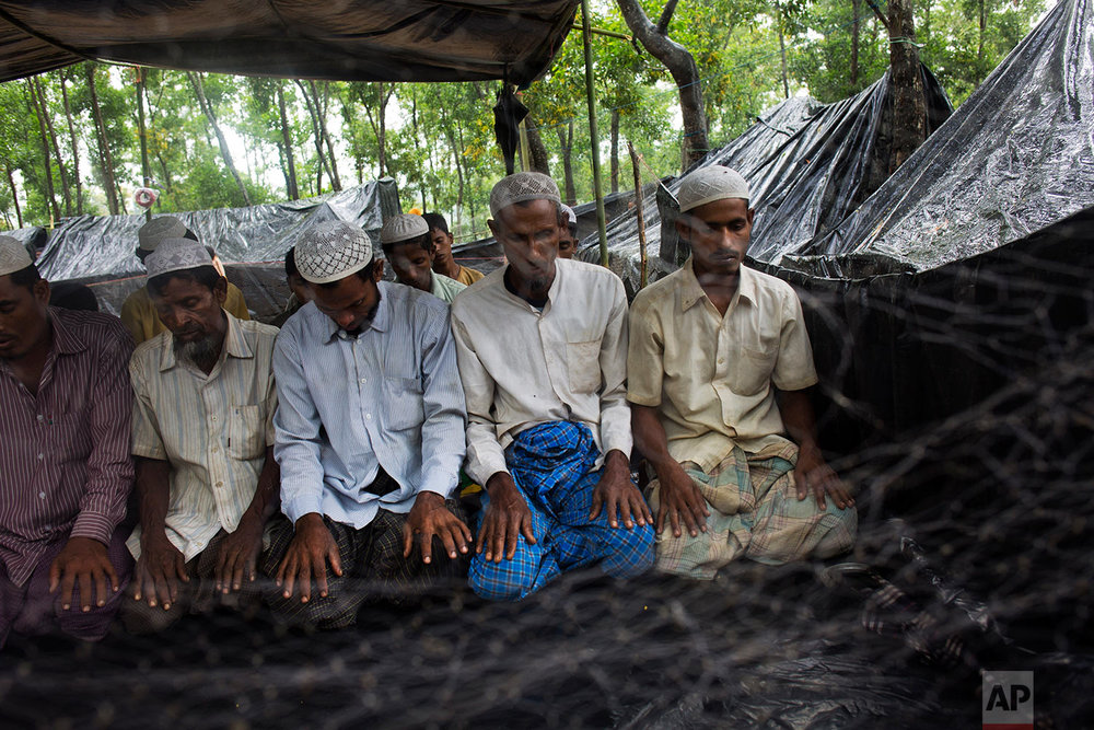 Rohingya Muslims, who have recently crossed over the border from Myanmar into Bangladesh, offer Friday prayers at a makeshift mosque in Kutupalong, Bangladesh, Friday, Sept. 8, 2017. (AP Photo/Bernat Armangue)
