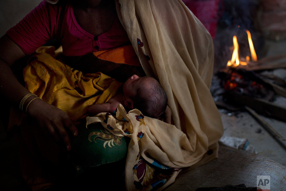 In this Thursday, Sept. 7, 2017 photo, 25-year-old Rohingya Muslim woman Zahida Begum cradles her few-hours-old son who she gave birth to alone in the toilet outside the room, at Kutupalong refugee camp, Bangladesh. Begum had crossed into Bangladesh on Sept. 1, with her two young sons, husband and mother, fleeing shootings and arson attacks by Myanmar army soldiers and local monks. Through hours of walking through this massive refugee camp, set up in the early 90s to accommodate the first waves of Rohingya Muslim refugees who started escaping convulsions of violence and persecution in Myanmar, Associated Press reporters could not spot a single doctor. There are no clinics or pharmacies or even basic first aid centers. (AP Photo/Bernat Armangue)