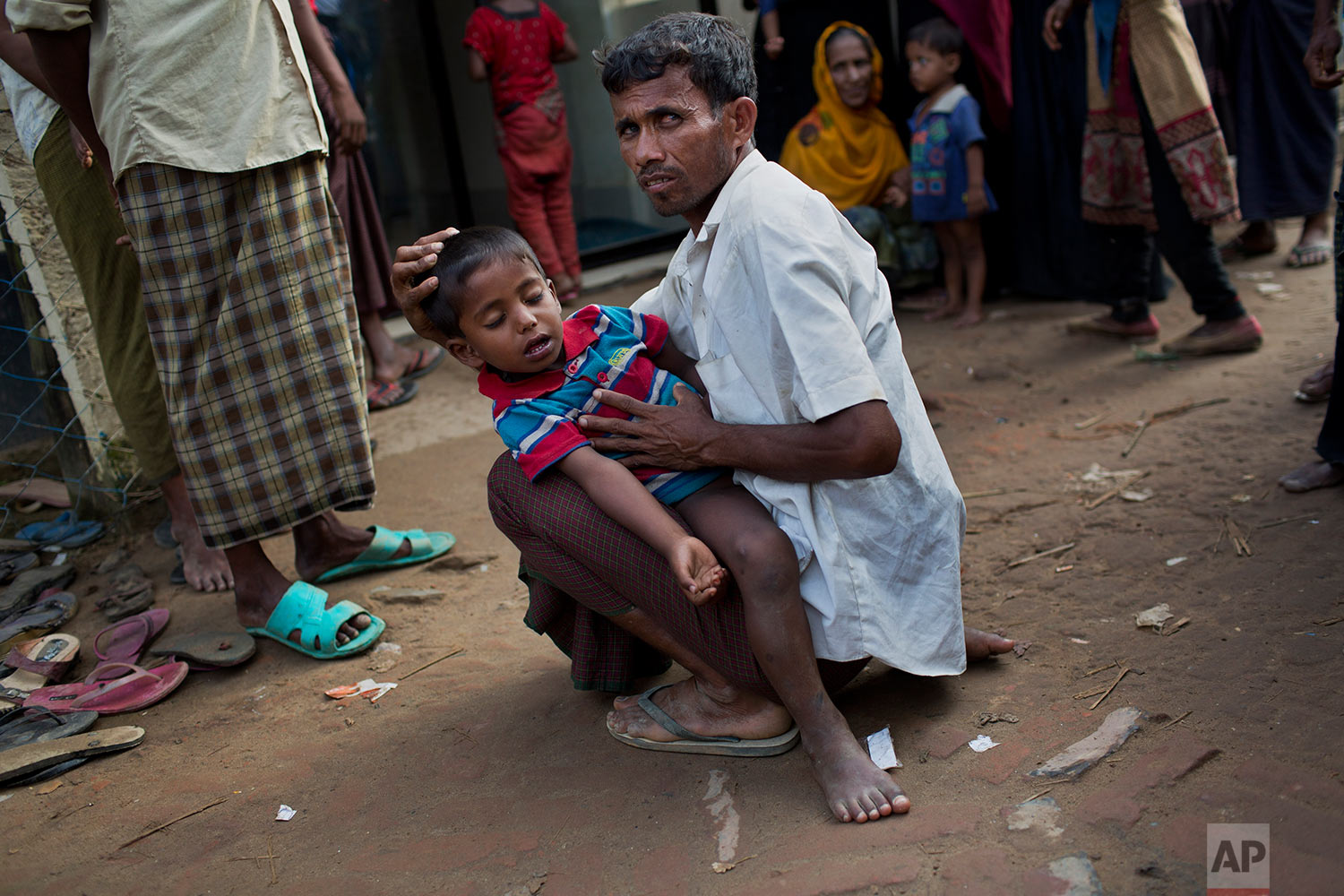 A Rohingya Muslim man holds a child with feveras they await treatment outside a clinic at Leda Refugee Camp, Bangladesh, Saturday, Sept. 9, 2017. (AP Photo/Bernat Armangue)