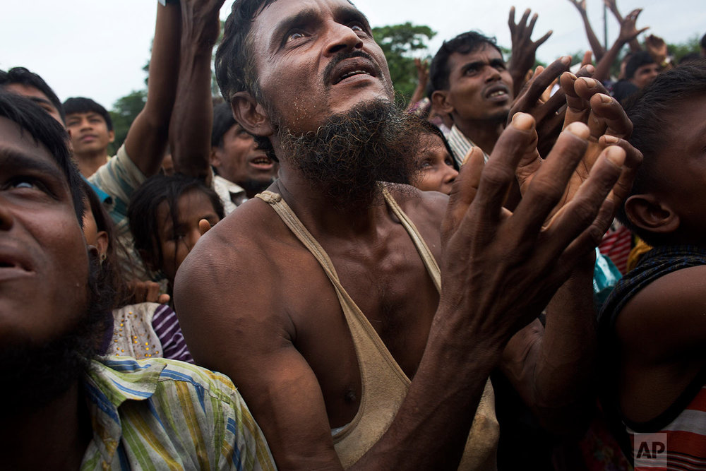 A Rohingya man stretches his arms out for food distributed by local volunteers, with bags of puffed rice stuffed into his vest at Kutupalong, Bangladesh, Saturday, Sept. 9, 2017. (AP Photo/Bernat Armangue)