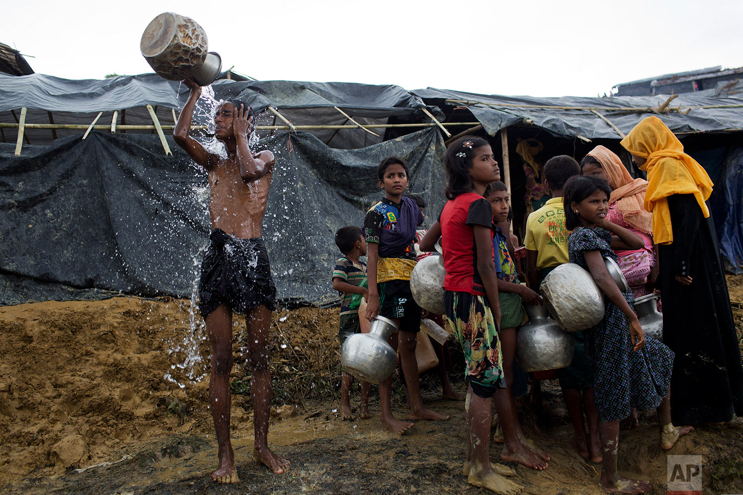 Newly arrived Rohingya wait to collect water from a tube well that was installed a few days ago, as a boy bathes beside them, at Ukhia, Bangladesh, Saturday, Sept. 9, 2017. (AP Photo/Bernat Armangue)