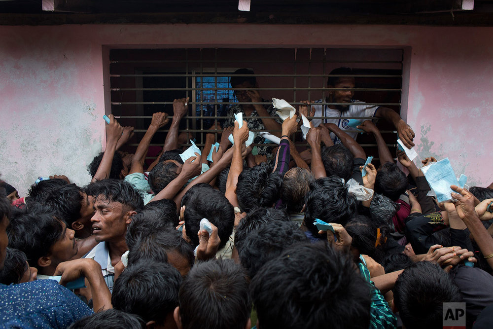 Newly arrived Rohingya try to get their tokens validated in order to collect a bag of rice distributed by aid agencies in Kutupalong, Bangladesh, Saturday, Sept. 9, 2017. (AP Photo/Bernat Armangue)