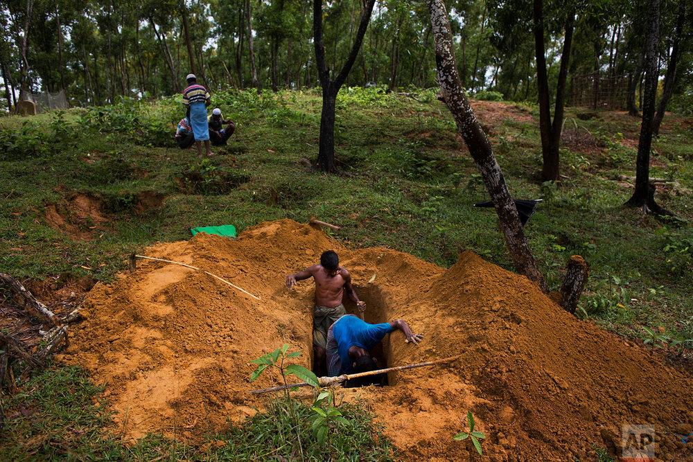 Rohingya men dig a grave in Kutupalong's refugee camp's cemetery, Bangladesh, Friday, Sept. 8, 2017. (AP Photo/Bernat Armangue)