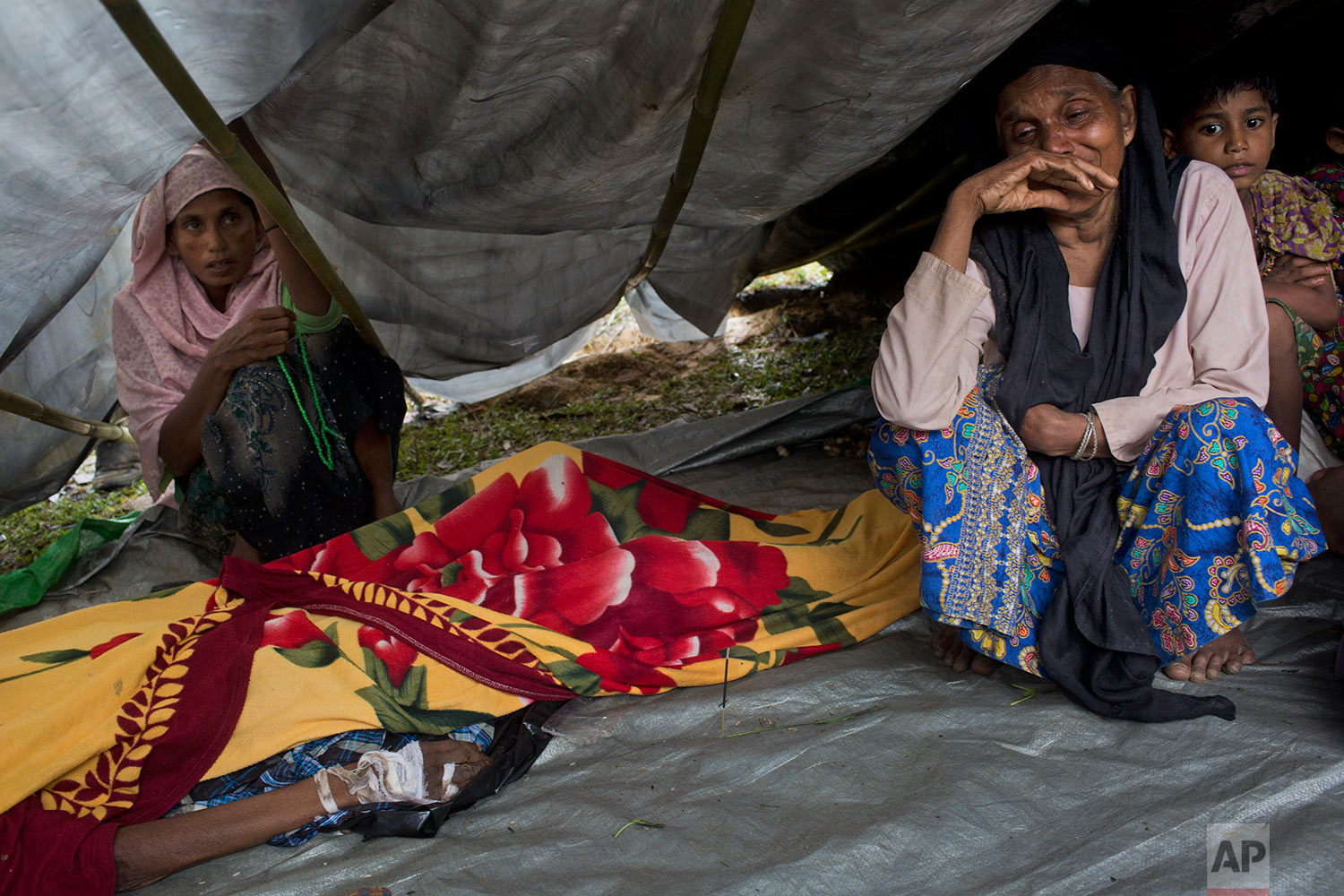 Newly arrived Rohingyas mourn by the body of a family member Ali Akbar, 70, in a makeshift tent in Kutupalong, Bangladesh, Friday, Sept. 8, 2017. According to family members, Akbar was shot in the hand and beaten with rifle butts by Myanmar soldiers before the family escaped to Bangladesh. He died today. (AP Photo/Bernat Armangue)