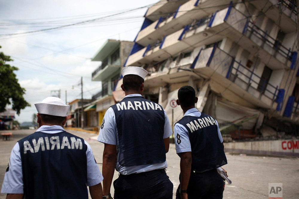 Three Navy sailors walk by the partially collapsed structure of an hotel in the town of Matias Romero, Oaxaca state, Mexico, Friday, Sept. 8, 2017. (AP Photo/Felix Marquez)