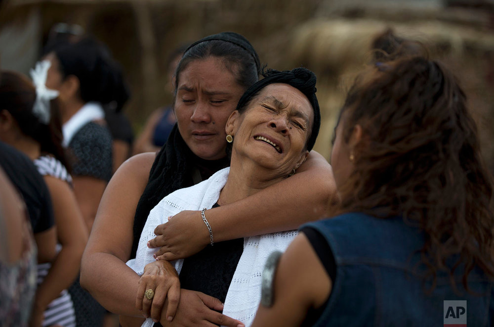 Mourners grieve at a funeral service for 90-year-old Hermilo Martinez, who relatives said died from fright following Thursday's magnitude 8.1 earthquake, in Juchitan, Oaxaca state, Mexico, Monday, Sept. 11, 2017. T(AP Photo/Rebecca Blackwell)