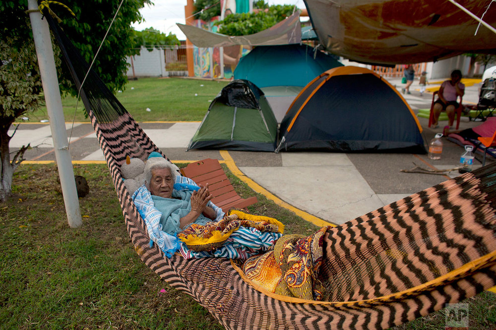 Manuela Lopez, 80, awakens in her hammock, at a technology school where people were sheltering after their homes were destroyed or damaged in Thursday's magnitude 8.1 earthquake, in Juchitan, Oaxaca state, Mexico, just after dawn, Monday, Sept. 11, 2017. (AP Photo/Rebecca Blackwell)