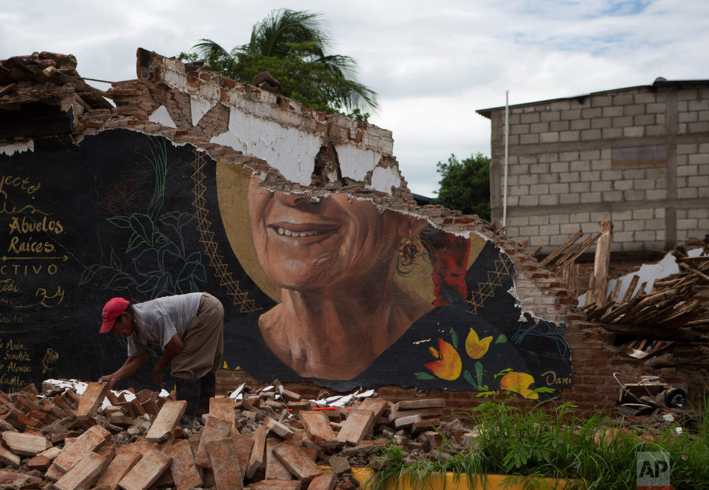 A man recovers bricks from a building destroyed in Thursday's magnitude 8.1 earthquake, in Union Hidalgo, Oaxaca state, Mexico, Sunday, Sept. 10, 2017. (AP Photo/Rebecca Blackwell)