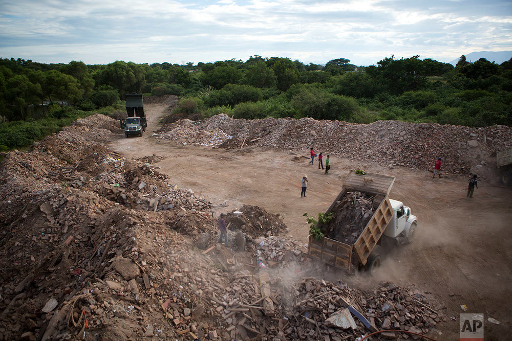 Dump trucks empty debris from homes and buildings destroyed in Thursday's magnitude 8.1 earthquake, in Asuncion Ixtaltepec, Oaxaca state, Mexico, Sunday, Sept. 10, 2017. (AP Photo/Rebecca Blackwell)