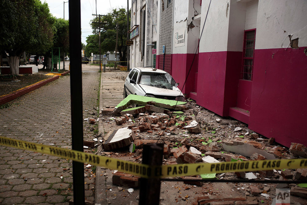 Rubble litters a sidewalk next to a damaged car in Matias Romero, Oaxaca state, Mexico, Friday, Sept. 8, 2017. (AP Photo/Felix Marquez)