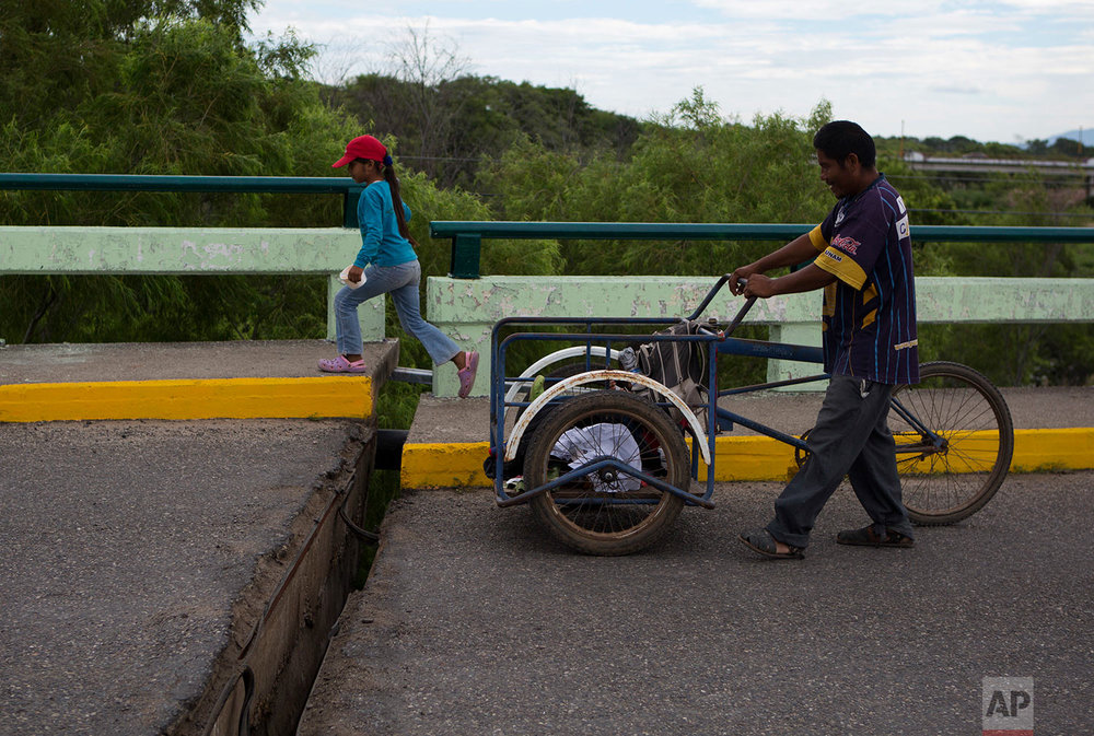 People cross a bridge whose sections separated and shifted apart during Thursday's magnitude 8.1 earthquake in Asuncion Ixtaltepec, Oaxaca state, Mexico, Sunday, Sept. 10, 2017. (AP Photo/Rebecca Blackwell)