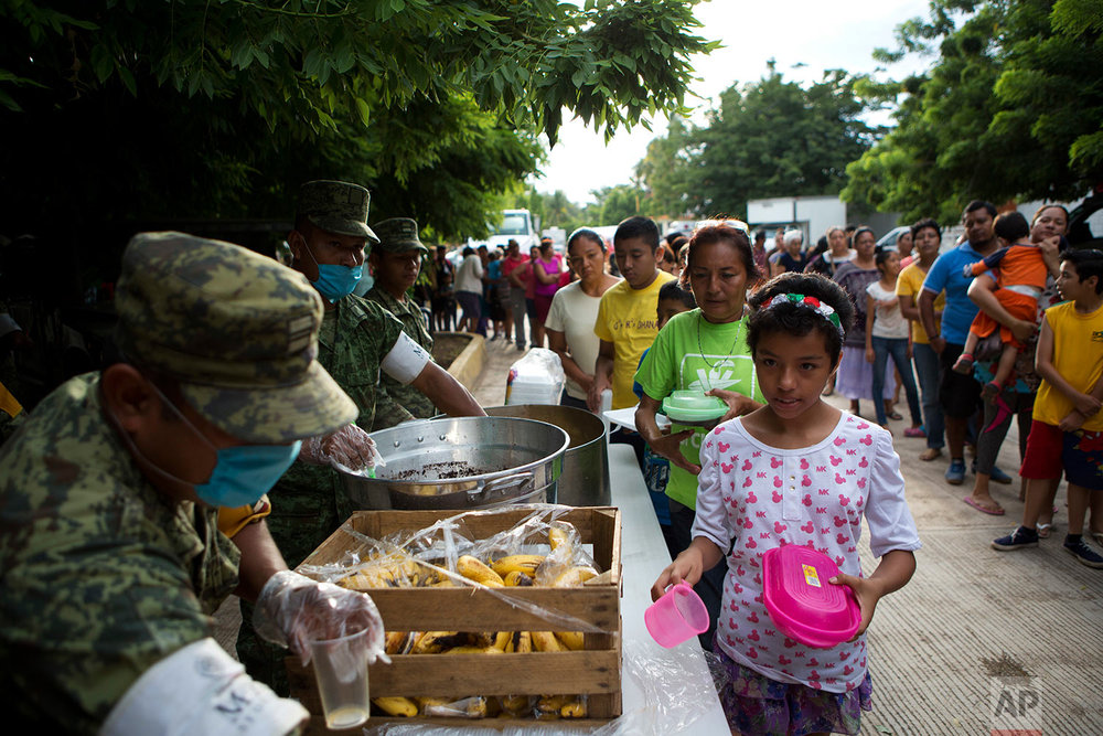Soldiers serve breakfast to people sheltering at a technology school after their homes were destroyed or damaged in Thursday's magnitude 8.1 earthquake, in Juchitan, Oaxaca state, Mexico, Monday, Sept. 11, 2017. (AP Photo/Rebecca Blackwell)