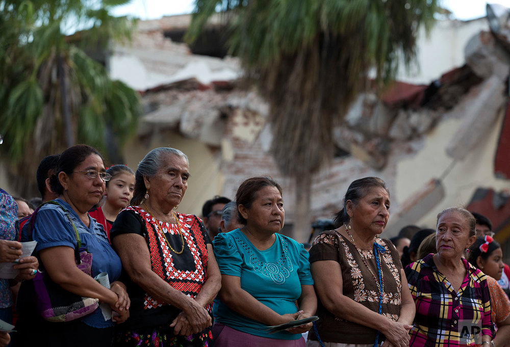 Catholics attend an open air Mass in a town square outside a damaged school, across the street from St. Vicente Ferrer church which was heavily damaged in Thursday's magnitude 8.1 earthquake, in Juchitan, Oaxaca state, Mexico, Sunday, Sept. 10, 2017. (AP Photo/Rebecca Blackwell)