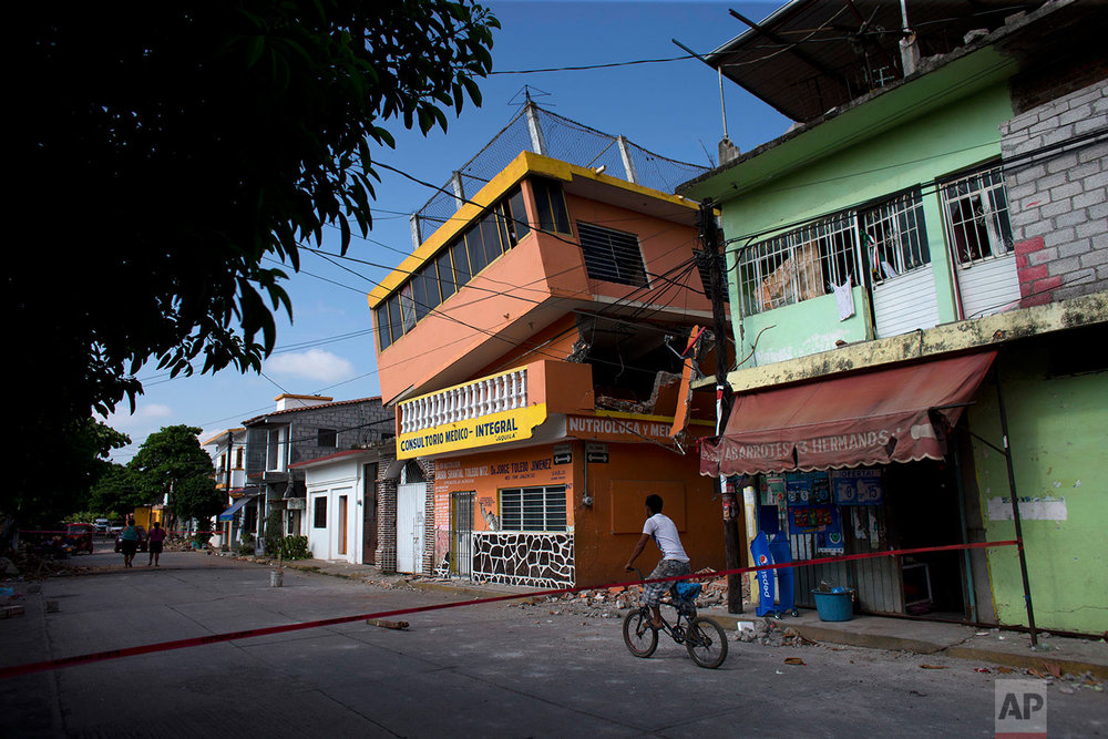A young man bikes past a partially collapsed building following a major earthquake, in Juchitan, Oaxaca state, Mexico, Saturday, Sept. 9, 2017. (AP Photo/Rebecca Blackwell)