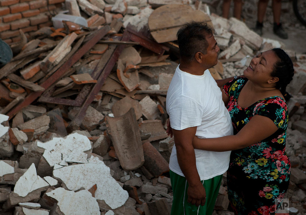 A woman tries to calm an angry man during a dispute over how soldiers should allocate rations, in a zone heavily affected by Thursday's magnitude 8.1 earthquake, in Juchitan, Oaxaca state, Mexico, Saturday, Sept. 9, 2017. (AP Photo/Rebecca Blackwell)