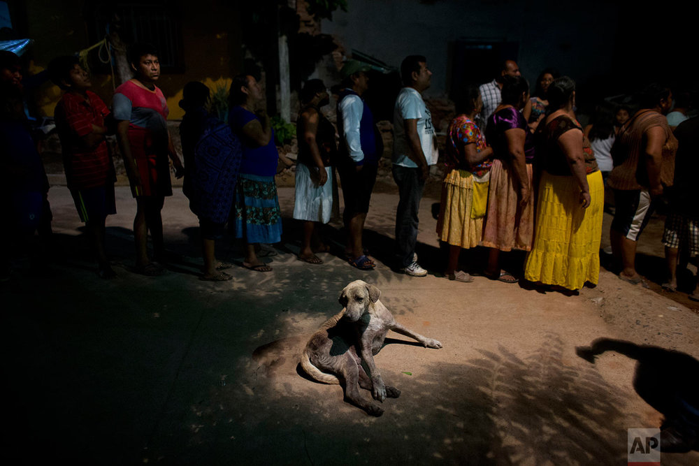 A dog lies alongside a line of people waiting to receive a plate of stewed mutton, tortillas, and rice distributed by a community group from neighboring El Espinal, in a zone heavily affected by Thursday's magnitude 8.1 earthquake in Juchitan, Oaxaca state, Mexico, Monday, Sept. 11, 2017. (AP Photo/Rebecca Blackwell)