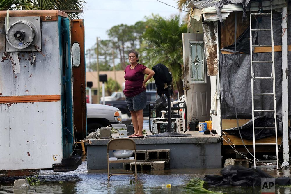In this Sept. 11, 2017 file photo, Elida Dimas looks at floodwaters from her porch, in the aftermath of Hurricane Irma, in Immokalee, Fla. Irma badly damaged Dimas' mobile home and destroyed another she and her husband used for rental income, making their tough life even harder. (AP Photo/Gerald Herbert)