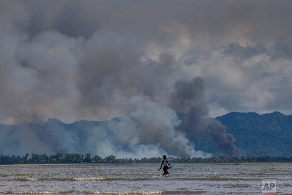 A Bangladeshi boy walks towards a parked boat as smoke rises from across the border in Myanmar, at Shah Porir Dwip, Bangladesh, Thursday, Sept. 14, 2017. Nearly three weeks into a mass exodus of (AP Photo/Dar Yasin)
