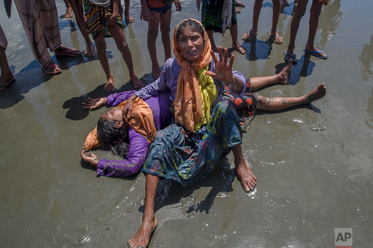 A Rohingya Muslim woman, who crossed over from Myanmar into Bangladesh, shouts for help as a relative lies unconscious after the boat they were traveling in capsized minutes before reaching shore at Shah Porir Dwip, Bangladesh, Thursday, Sept. 14, 2017.  (AP Photo/Dar Yasin)