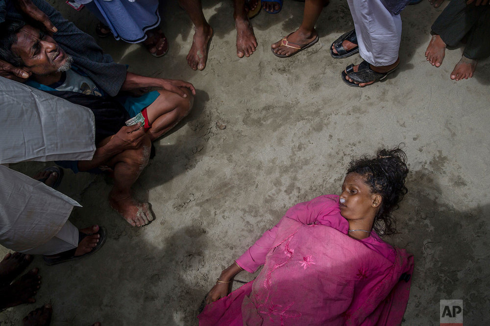 A Rohingya Muslim man Mohammad Islam sits beside the body of his daughter-in-law Anwara Begum who died when the boat they were traveling in capsized minutes before reaching shore in Shah Porir Dwip, Bangladesh, Thursday, Sept. 14, 2017. (AP Photo/Dar Yasin)