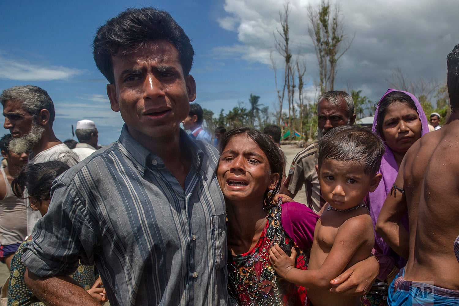Rohingya Muslims, who crossed over from Myanmar into Bangladesh, mourn for a family member who drowned when the boat they were traveling in capsized minutes before reaching the shore, at Shah Porir Dwip, Bangladesh, Thursday, Sept. 14, 2017. (AP Photo/Dar Yasin)