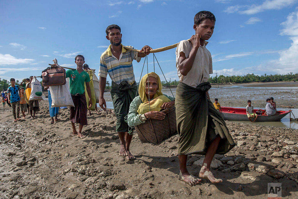 Rohingya Muslims, who crossed over from Myanmar into Bangladesh, carry an elderly woman in a basket and walk towards a refugee camp in Shah Porir Dwip, Bangladesh, Thursday, Sept. 14, 2017. Nearly three weeks into a mass exodus of  (AP Photo/Dar Yasin)