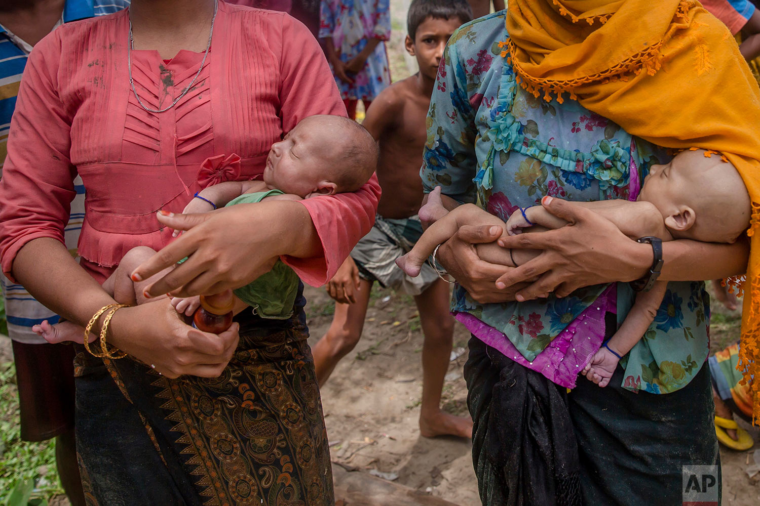 A Rohingya Muslim woman Hanida Begum, right, who crossed over from Myanmar into Bangladesh, holds her infant son Abdul Masood who died when the boat they were traveling in capsized minutes before reaching shore, as a relative holds Masood's twin brother, in Shah Porir Dwip, Bangladesh, Thursday, Sept. 14, 2017. (AP Photo/Dar Yasin)